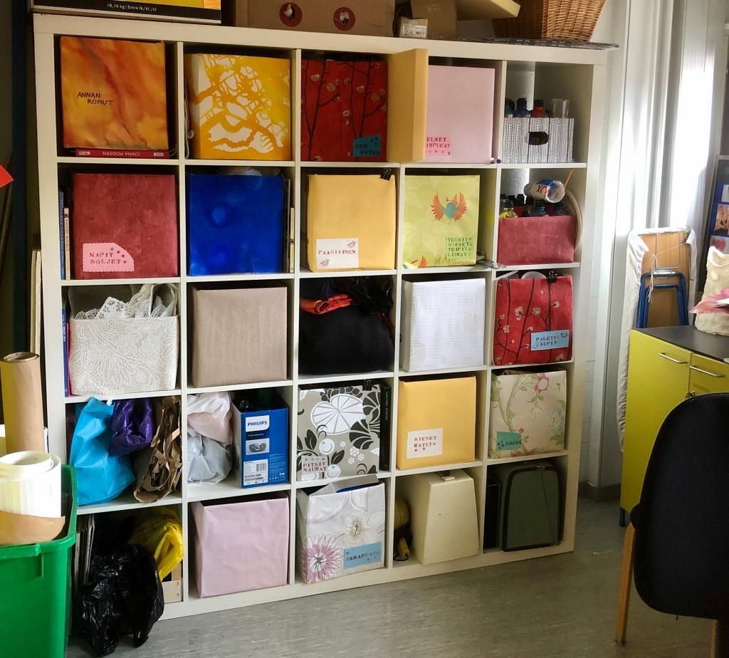 Värikkäitä laatikoita hyllyssä.