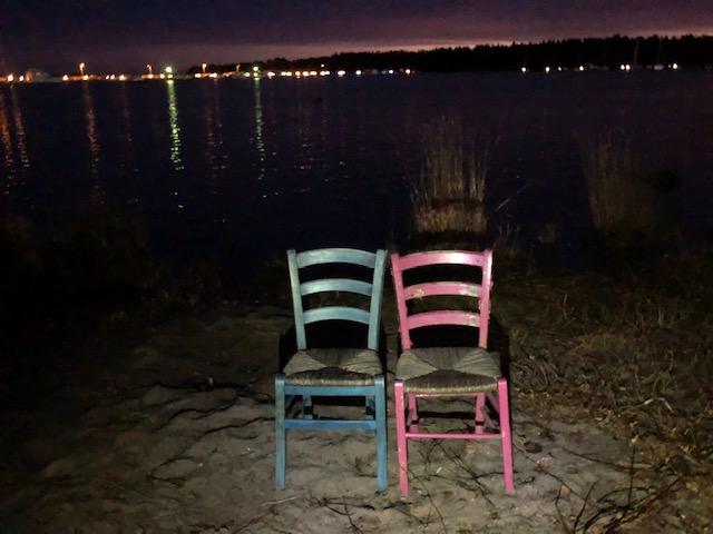 Kaksi tuolia merenrannalla. Vaaleanpunainen ja turkoosin värinen puutuoli. Sataman valoja iltahämärässä.